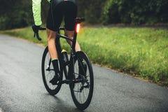 Мужской велосипедист практикуя на влажной дороге Стоковое Изображение