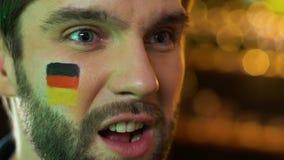 Мужской вентилятор с немецким флагом на осадке щеки о любимой безнадежной игре спортивной команды видеоматериал