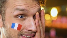 Мужской вентилятор с французским флагом на осадке щеки о любимой безнадежной игре спортивной команды сток-видео