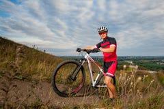 Мужской велосипедист горы отдыхая около его велосипеда Стоковое Изображение RF