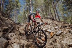 Мужской велосипедист спортсмена идя вниз с холма над камнями Стоковые Фотографии RF