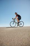 Мужской велосипед катания велосипедиста на плоской дороге Стоковое Фото