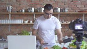 Мужской видео- блоггер в белой футболке и стеклах говоря как сварить зеленые овощи сток-видео