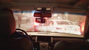 Мужской водитель в автомобиле стоя в заторе движения перед белым автомобилем в нерезкости акции видеоматериалы