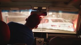 Мужской водитель в автомобиле стоя в заторе движения перед белым автомобилем в нерезкости сток-видео