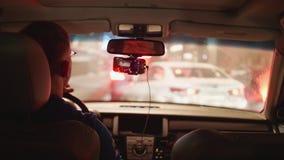 Мужской водитель в автомобиле стоя в заторе движения перед белым автомобилем в нерезкости видеоматериал