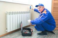 Мужской водопроводчик исправляет утечка Регулируемый ключ затянуть уплотнения струбцин гайки, изоляты стоковое фото rf