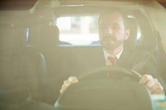 Мужской водитель автомобиля сфокусированный на дороге Стоковые Фотографии RF