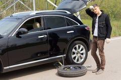 Мужской водитель изменяя его покрышку автомобиля после прокола Стоковые Изображения RF