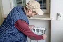 Мужской водопроводчик ремонтируя радиатор с ключем Стоковые Изображения RF