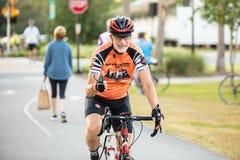Мужской всадник велосипеда дает большие пальцы руки камеры вверх по мере того как он причаливает стоковая фотография