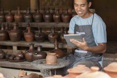 Мужской гончар используя цифровую таблетку в мастерской гончарни стоковое фото rf