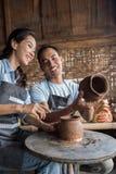 Мужской гончар помогая женскому гончару стоковое изображение