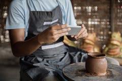 Мужской гончар фотографируя его продукт в мастерской гончарни стоковые фотографии rf
