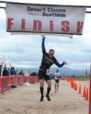 Мужской гонщик при оружия поднятые и перепрыгнутые вверх по пересекать финишную черту Стоковое Фото