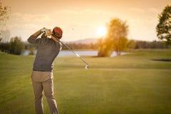Мужской гольф-клуб игрока гольфа отбрасывая на сумраке Стоковая Фотография