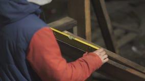 Мужской гравер проверяя вровень деревянной планки сток-видео