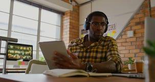 Мужской график-дизайнер слушая музыку пока работающ на столе 4k акции видеоматериалы