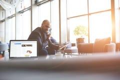 Мужской главный исполнительный директор сидит около открытой сет-книги с интернет-страницей на экране Стоковые Фотографии RF