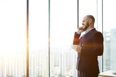Мужской главный исполнительный директор стоит с чашкой кофе в руке в его офисе около предпосылки окна с космосом экземпляра стоковые фото