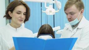 Мужской дантист и женский ассистент обсуждают диагноз пациента средства Дантисты женщины и человека спорят тесты пациента сток-видео
