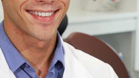 Мужской дантист усмехаясь при совершенные зубы держа зубную щетку видеоматериал