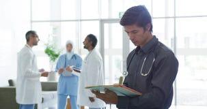 Мужской доктор в улыбках больницы к камере 4k акции видеоматериалы