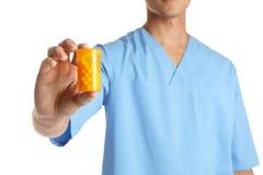 Мужской доктор держа бутылку таблетки на белом, крупный план медицинский предмет стоковое изображение rf