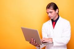 Мужской доктор держа компьтер-книжку в его оружиях стоковое изображение