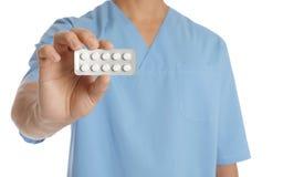Мужской доктор держа таблетки на белой предпосылке медицинский предмет стоковое фото