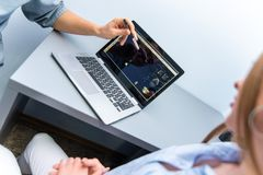 Мужской доктор и пациент девушки сидят около ноутбука и говорить стоковая фотография rf
