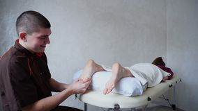 Мужской доктор массажирует ноги маленькой девочки которая лежит на кресле в ярком медицинском салоне видеоматериал