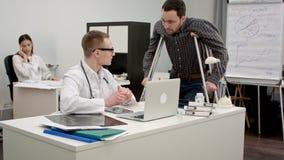 Мужской доктор обсуждая рентгеновский снимок позвоночника с пациентом на костылях Стоковое фото RF