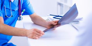 Мужской доктор объясняя рентгеновский снимок позвоночника к пациенту в медицинском офисе Стоковые Изображения