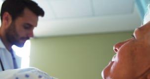 Мужской доктор показывая медицинское заключение к старшей женщине на цифровой таблетке сток-видео