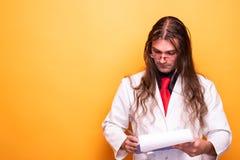 Мужской доктор смотря доску сзажимом для бумаги рецепта стоковые фото