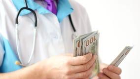 Мужской доктор считая конец-вверх долларов Развращение в медицине стоковое фото