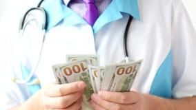 Мужской доктор считая конец-вверх долларов Развращение в медицине стоковое изображение