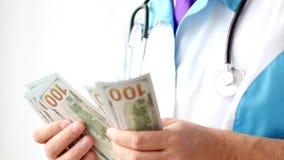 Мужской доктор считая конец-вверх долларов Развращение в медицине стоковые изображения rf