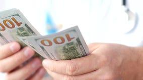 Мужской доктор считая конец-вверх долларов Развращение в медицине стоковое изображение rf