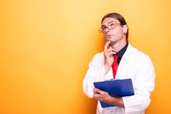 Мужской доктор с его думать ручки и доски сзажимом для бумаги стоковая фотография rf