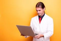 Мужской доктор хмурясь к дисплею компьтер-книжки стоковая фотография rf