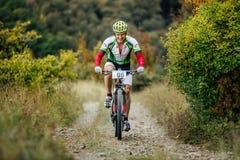 Мужской ехать велосипедиста всадника гористый на горной тропе с улыбкой на стороне Стоковое Изображение RF