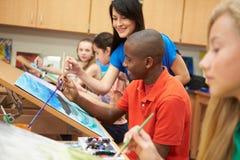 Мужской зрачок в художественном классе средней школы с учителем стоковое фото rf