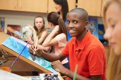 Мужской зрачок в художественном классе средней школы стоковые изображения rf