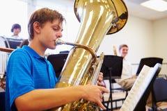 Мужской зрачок играя тубу в оркестре средней школы стоковое фото rf