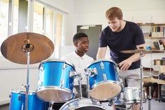 Мужской зрачок при учитель играя барабанчики в уроке музыки стоковые фотографии rf