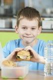 Мужской зрачок сидя на таблице в еде здоровом p школьного кафетерия стоковое изображение rf