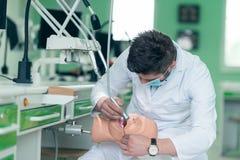 Мужской зубоврачебный студент практикуя на кукле Стоковые Фотографии RF