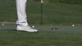 Мужской игрок в гольф кладя шар для игры в гольф внутри для того чтобы продырявить видеоматериал